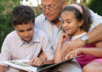 Photo of a grandfather reading to his grandchildren. Link to Life Stage Gift Planner Over Age 70 Gifts.